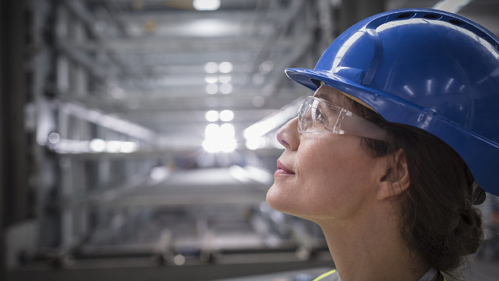 Female Factory Worker In A Blue Hard Hat Stock Photo